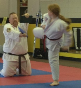 Savannah qualifying for her black belt with Dad holding her boards.